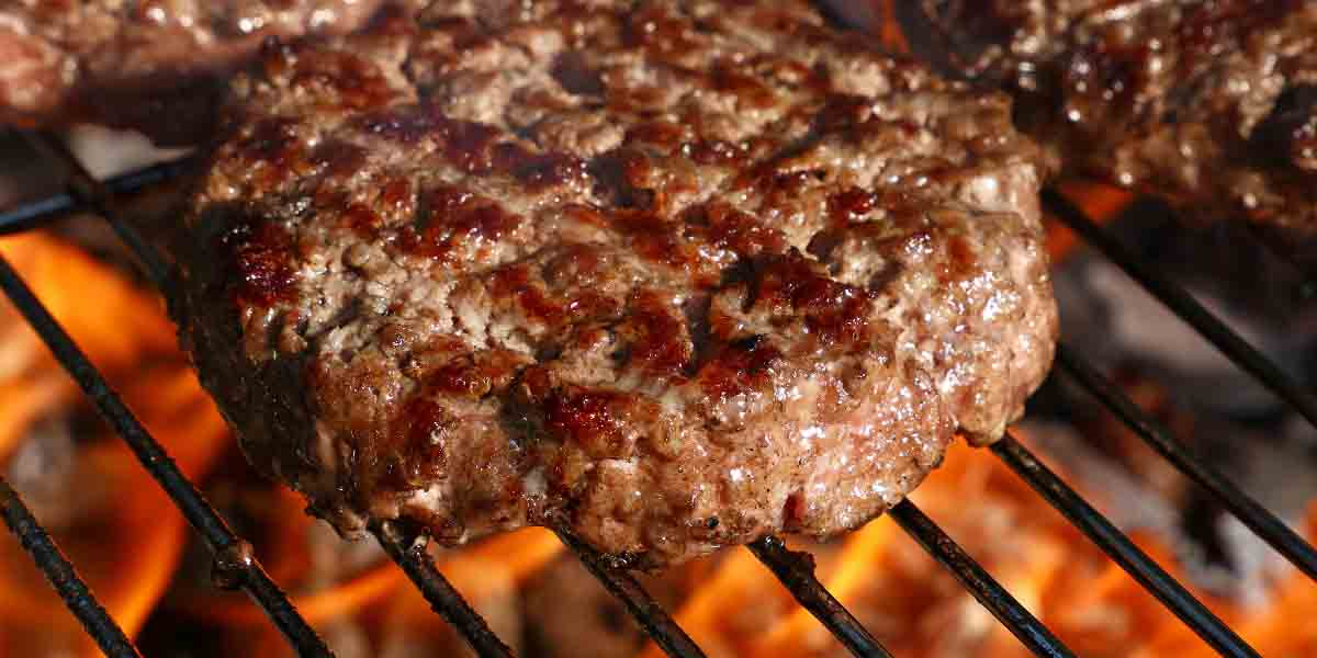 Close up beef burgers for hamburger prepared grilled on bbq fire flame grill